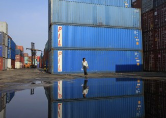 A worker walks in front of shipping containers at the Port of Yangon. (Photo: Reuters)