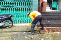 A municipal worker tries to unblock a sewage drain in a Rangoon alleyway. (PHOTO: DVB)