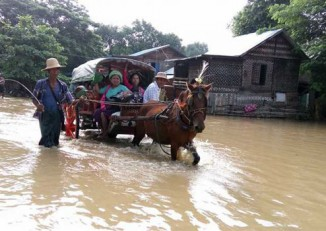 Taungdwingyi residents deal with the floodwaters that inundated the town after sluice gates on a reservoir were ordered open on 22 September 2016. (PHOTO: DVB)
