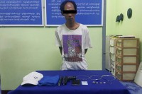 "Suspected thief ""Mr. Rachan"" of Thailand poses for a police photo with goods he allegedly stole from a jewellery store in Tachilek. (Photo: Myanmar Police Force)"