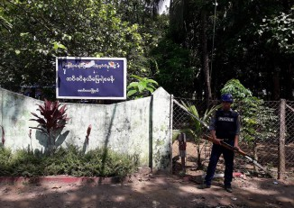 A member of Burma's border police force stands guard outside a police outpost in Arakan State's Maungdaw Township. (Photo: DVB)
