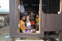 File photo from 2014 of a family in Myaing Thar Yar, a resettlement village built by the Burmese government as compensation for villagers who previously lived on land now used as part of the Thilawa SEZ. (Photo: CI Smith / DVB)