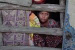 A Rohingya woman sits inside a shelter in this file photo from 2012. (Photo: Pete Pattison)
