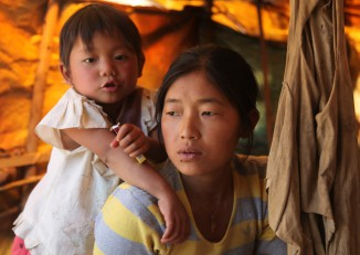 A refugee from Bhamo township waits with young her daughter at the Jegau camp in KIO-controlled territory near the Chinese border (Feb 14 2012). She fled her home in July 2011, one month after the start of the conflict. (Photo: Seamus Martov)
