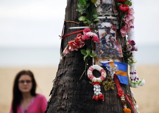A woman looks at a tree decorated with flowers and pictures as people gather for a Swedish memorial service for victims of the 2004 tsunami at a beach in Khao Lak on 26 December 2014. (Photo: Reuters)