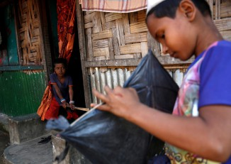 A Rohingya boy looks on as another boy makes a kite in the Leda unregistered Rohingya refugee camp in Cox's Bazar, Bangladesh, on 22 November 2016. (Photo: Reuters)