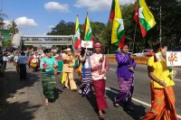 "A man (centre) in traditional Arakanese dress carries a Myanmar flag at a rally in Rangoon on 18 December. In front of him, a woman (yellow blouse) carries a ""Rakhine"" sign, while the woman behind him has a sign reading ""Shan"". (PHOTO: DVB)"