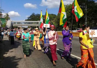 """A man (centre) in traditional Arakanese dress carries a Myanmar flag at a rally in Rangoon on 18 December. In front of him, a woman (yellow blouse) carries a """"Rakhine"""" sign, while the woman behind him has a sign reading """"Shan"""". (PHOTO: DVB)"""