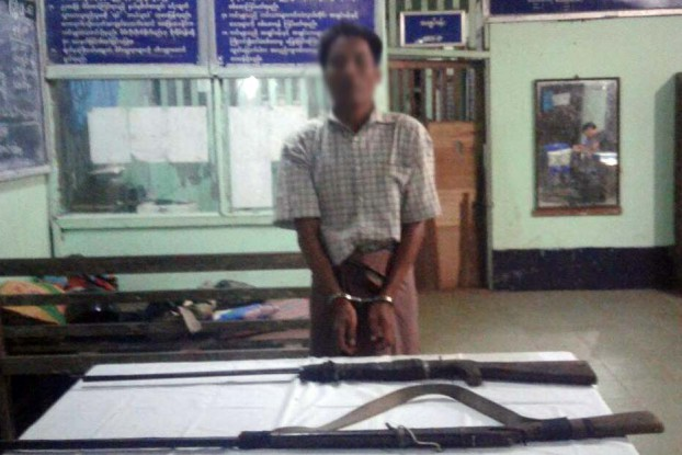 One of seven poaching suspects poses with two bolt-action rifles confiscated by police in Taikkyi township.
