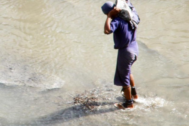 A prisoner shackled on both of his legs carries a granite stone at a rock quarry run by the prison department in Paung Township. (Swe Win / Myanmar Now)