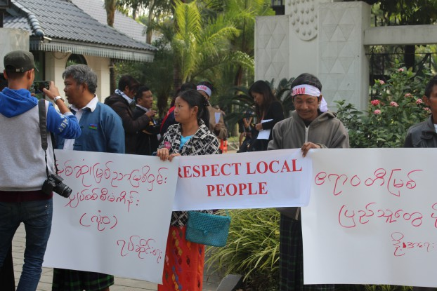 Protestors hold placards outside the Palm Spring Resort hotel in Myitkyina on Tuesday. (Photo: Kachin Development Networking Group)