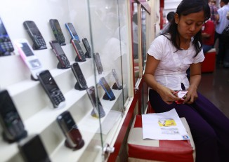 A woman fills up a form as she buys a SIM card in a phone shop in Rangon on 31 July 2014. (Photo: Reuters)