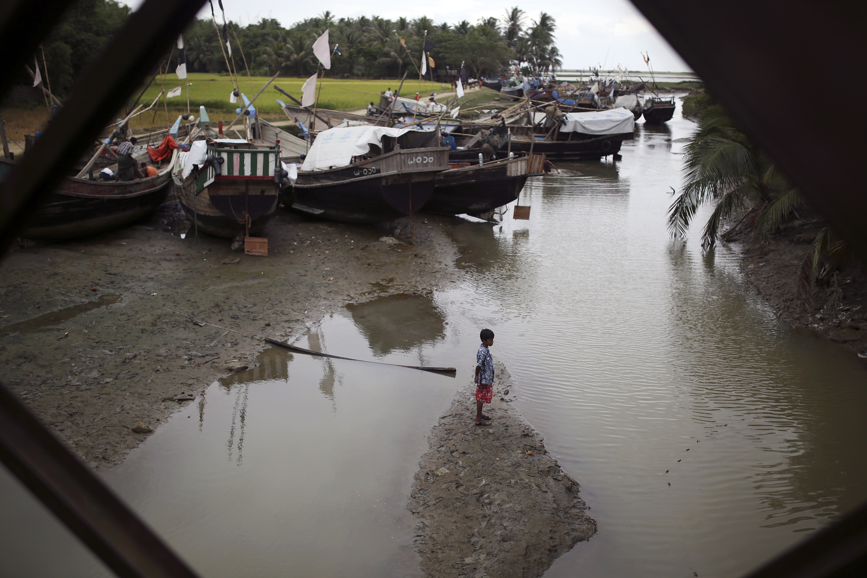 A boy stands on a sandbank near Rohingya fishermen working on their boats at Thae Chaung IDP camp outside Sittwe, Arakan State, on 7 November 2014. (Photo: Reuters)