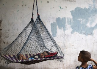 A son of a migrant fisherman from Burma rests in a hammock at a former shrimp warehouse where his family lives in Ban Nam Khem, a small fishing village on Thailand's Andaman Sea coast, on 13 December 2014. (Photo: Reuters)   ATTENTION EDITORS: PICTURE 13 OF 29 FOR WIDER IMAGE PACKAGE 'INDIAN OCEAN TSUNAMI - 10 YEARS ON'  SEARCH 'DAMIR TSUNAMI' FOR ALL IMAGES - RTR4IMSL