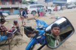 A United Wa State Army (UWSA) soldier reflected in a mirror as he sits on a motorbike in a market at Mongmao, Wa territory, in Burma's Shan State on 1 October 2016. (Photo: Reuters)