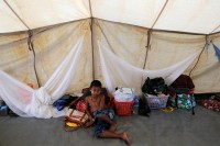 An Arakanese Buddhist boy who fled from recent violence in Maungdaw passes his time in a temporary shelter at a stadium in Sittwe, Burma on 25 October, 2016. (PHOTO: REUTERS)