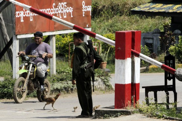 A soldier stands guard at the checkpoint in Burma's Payathonzu district, opposite the Three Pagodas Pass near the border with Thailand on 7 November 2010. (Photo: Reuters)
