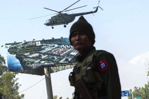 A Burmese Army soldier secures the ground while a military helicopter carrying troops takes off from Muse, northern Shan State, on 25 November 2016. (Photo: AFP)