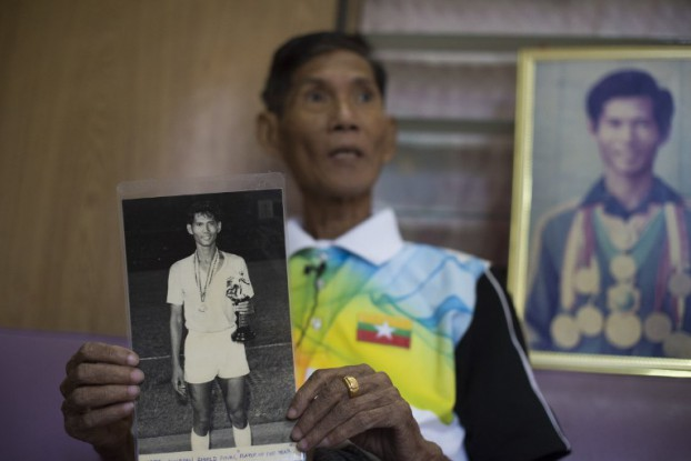 Myo Win Nyunt, 71, a former footballer, holds up a picture of himself as a player on Burma's national team during an interview in Rangoon on 26 January 2017.  (Photo: AFP)