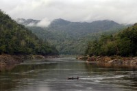Ethnic Karen men use a boat to cross the Salween River, Southeast Asia's longest undammed waterway, from Burma to Thailand in 12 May 2006. (Photo: Reuters)