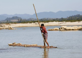 A man rows his bamboo raft to cross the Irrawaddy River near Bahalminhtin Bridge, near the town of Myitkyina in Kachin State, on 7 January 2010. (Photo: Reuters)