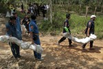 Rescue workers carry body bags with human remains, thought to include those of Rohingya Muslims, retrieved from a mass grave at a rubber plantation in Thailand's southern Songkhla province on 6 May 2015. (Photo: Reuters)
