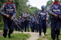 Policemen carry their weapons as they arrive in Sittwe on 10 June 2012. (Reuters)
