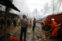 In this file picture from June 2012, policemen stand guard as firemen work to extinguish a fire during fighting between Buddhist Rakhines and Muslim Rohingyas in Sittwe. (PHOTO: REUTERS)