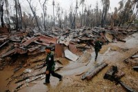 In this file photo from 2012, police officers inspect the aftermath of damage after a bout of communal rioting in Arakan State (PHOTO: Reuters)