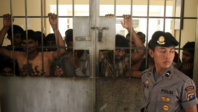 A police officer stands guard near illegal migrants from Burma at an immigration detention centre in Medan in Indonesia's North Sumatra province on 5 April 2013. (Reuters)
