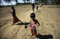 A young boy carries a ration of meat distributed as aid in Owntaw refugee camp near Sittwe. (PHOTO: Reuters)