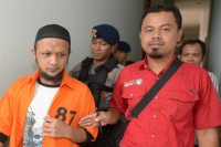 Achmad Taufiq, left,was also sentenced to seven years in prison for involvement in the embassy bomb plot. He is seen here guarded by police prior to a hearing in Jakarta, November 2013. (PHOTO: AFP)