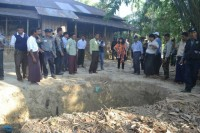 Local officials and international relief workers gather at the alleged site where clothing belonging to a Maungdaw police sergeant was found on January 14. (PHOTO: President's Office)