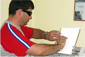 A blind man reads his ballot paper in Albania, when in 2005, the country allowed blind people to vote independently for the first time. (PHOTO: OSCE).