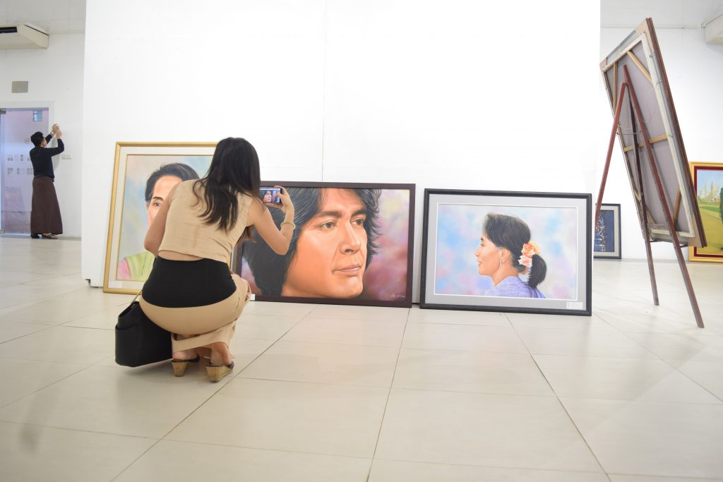 A young woman photographs some of the works at The Yangon Gallery. (PHOTO: Kimberley Phillips / DVB)